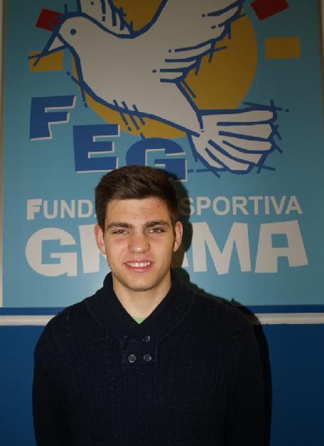 El portero del primer equipo de la F.E.Grama, Enric Avellaneda, posa ante un escudo en el Nou Municipal de Santa Coloma
